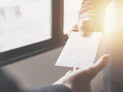 Pai a entregar envelope com cheque a filho
