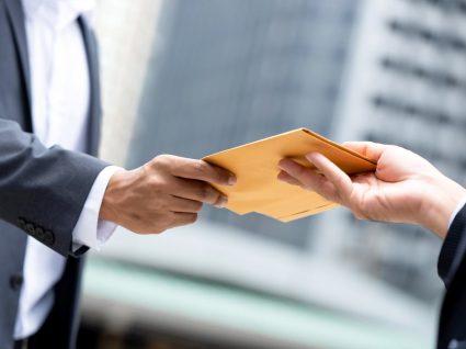 homem entrega envelope a outro com uma doação em dinheiro