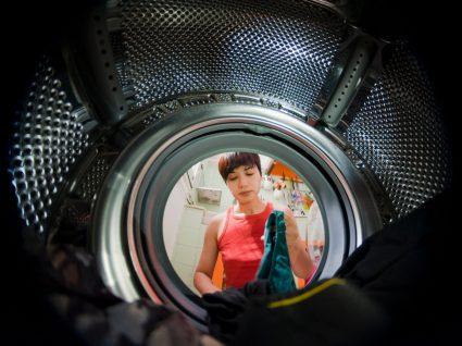 mulher a por roupa dentro da máquina para lavar