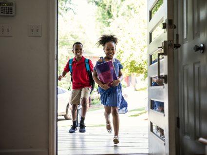 crianças a chegar a casa a celebrar as férias escolares