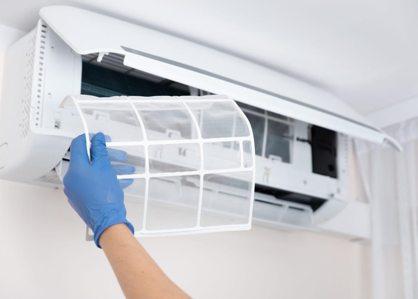 pessoa a limpar o filtro do ar condicionado