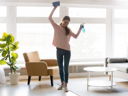mulher com hábitos das pessoas que tem sempre a casa limpa a arrumar a sala