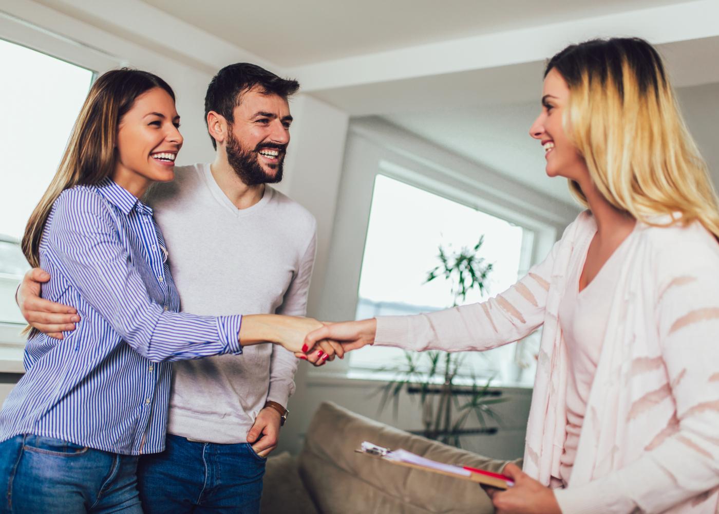 jovem casal a cumprimentar agente imobiliária