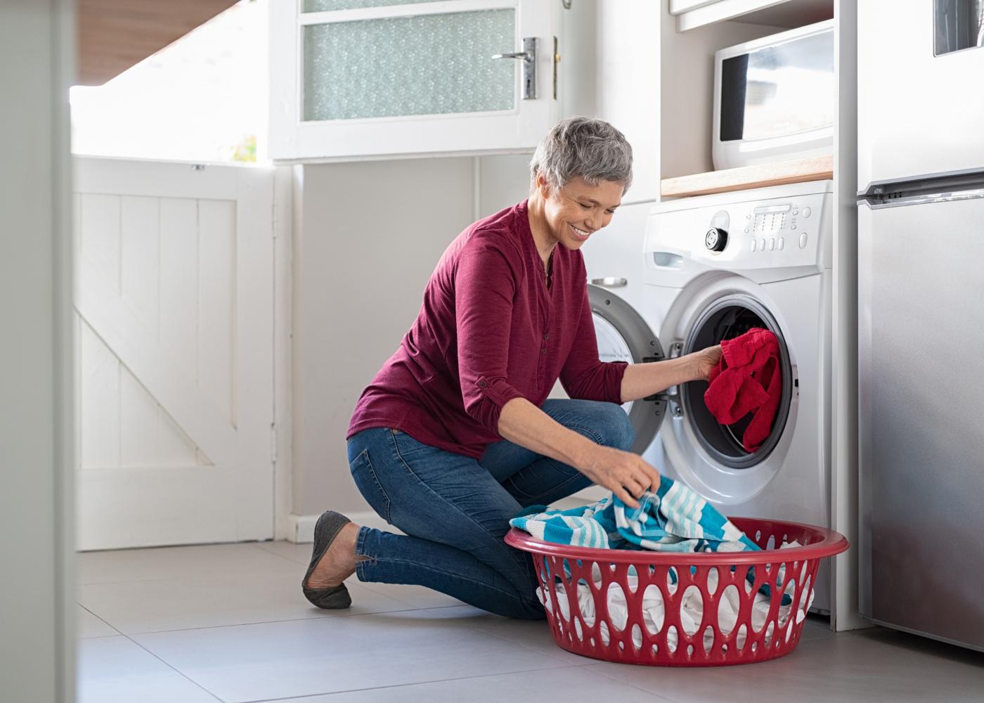 mulher a por a roupa na máquina de lavar