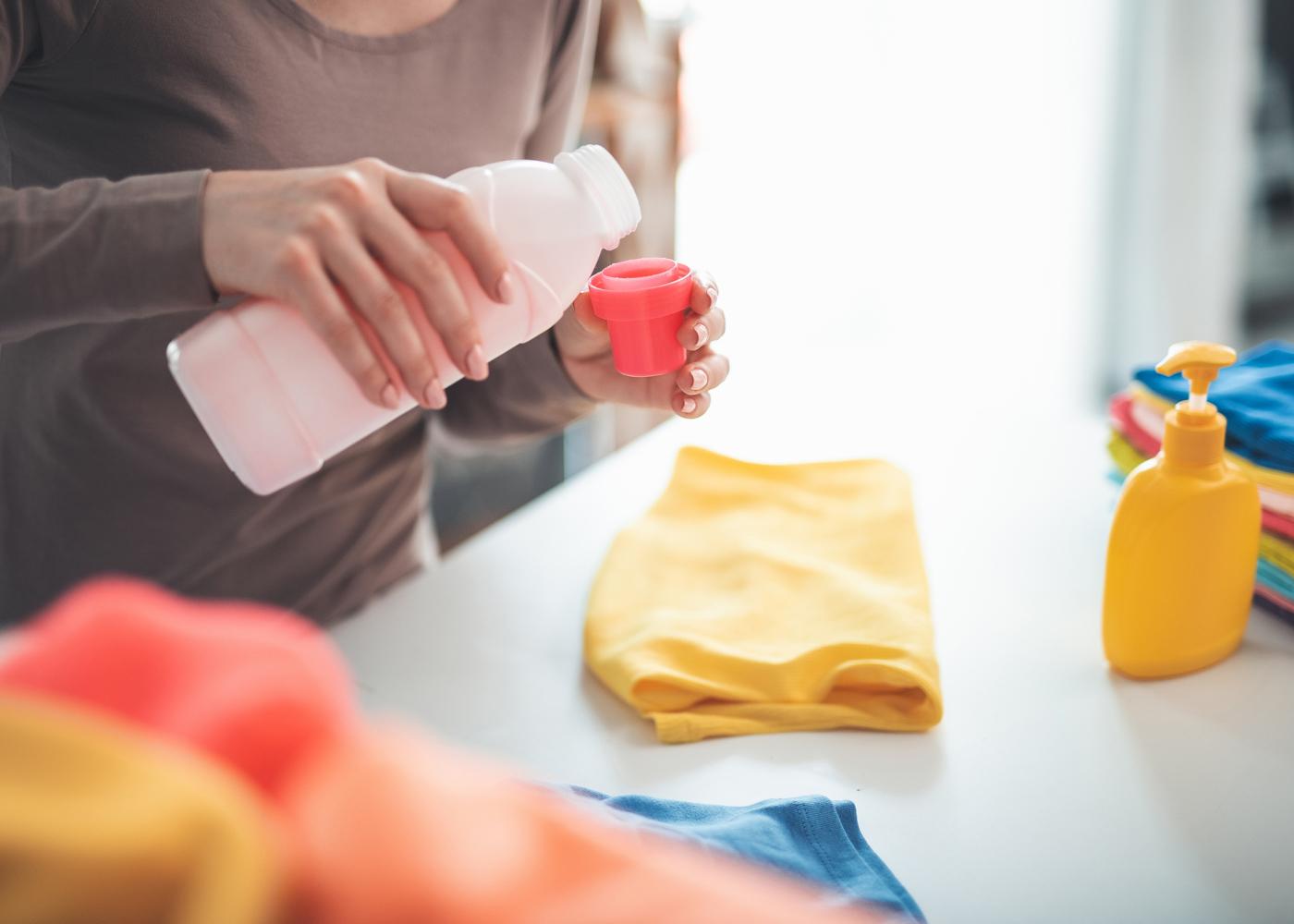 mulher a por detergente para lavar roupa