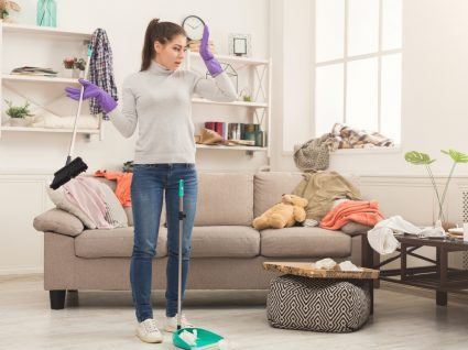 mulher na sala desarrumada a pensar como vai limpar a casa numa hora