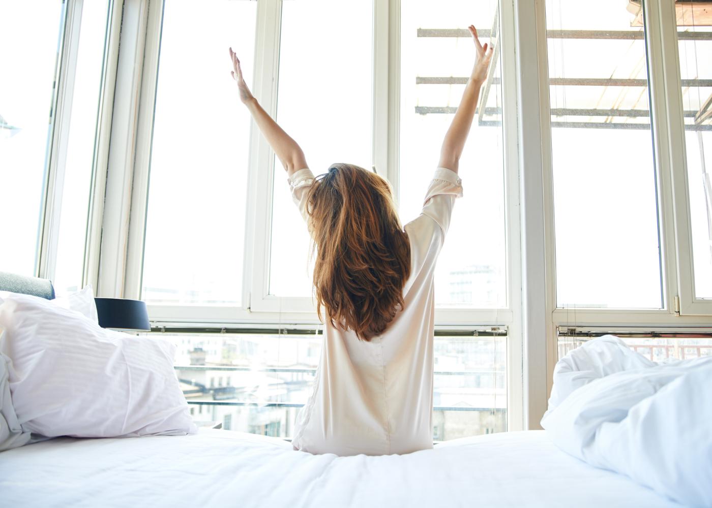 mulher sentada na cama com braços esticados a olhar pela janela