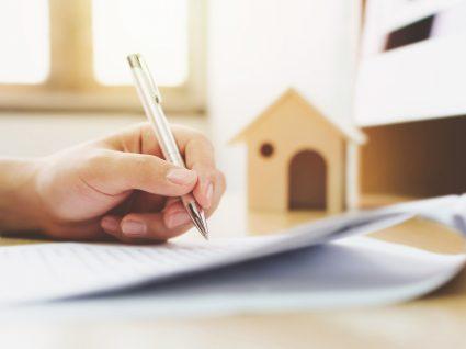pessoa a assinar contrato de arrendamento e verificar caderneta predial