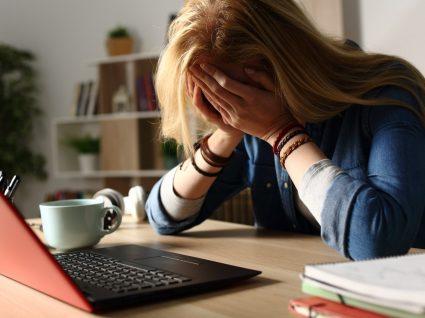 mulher ao computador com mãos na cabeça por exercer uma das profissões que causam mais stress