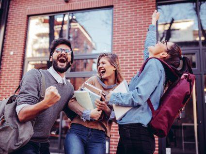 três estudantes felizes a festejar na rua