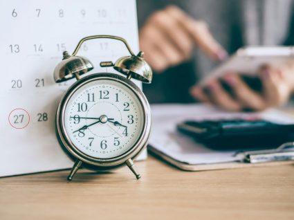 pessoa com relógio e calendário na mesa a consultar dicas para cumprir prazos