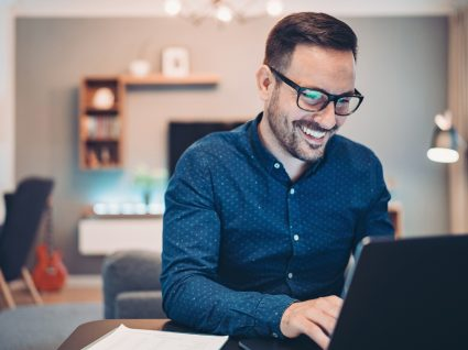 homem ao computador a exercer um dos empregos mais bem pagos e com menos stress