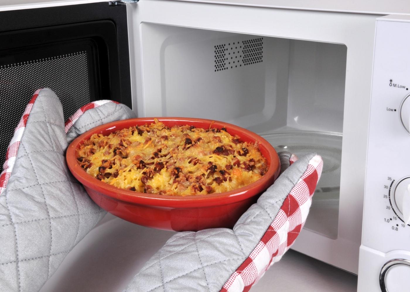 pessoa a colocar comida no microondas