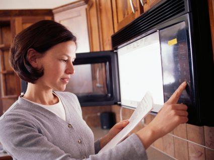 mulher a ler instruções para não cometer os erros mais comuns ao usar o microondas