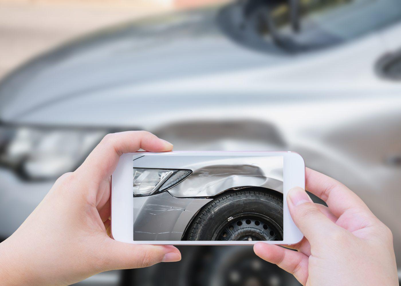 pessoa a fotografar carro danificado