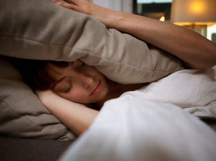 mulher a tentar dormir com almofada a tapar ouvidos