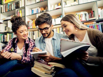 três estudantes numa biblioteca com livros e cadernos