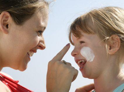 Mão a aplicar protetor solar para o rosto na filha