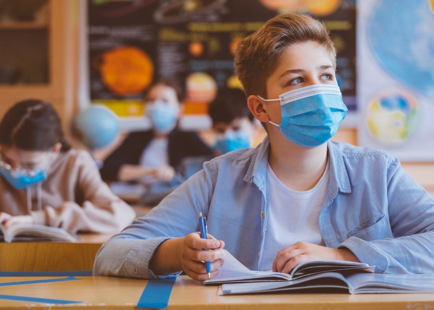 jovem com máscara na sala de aula