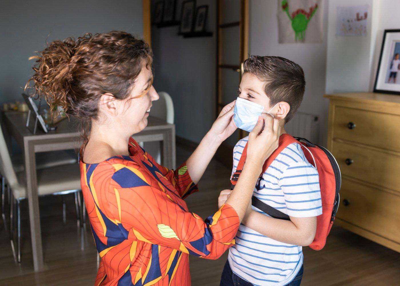 mãe a ajudar o filho a colocar a máscara no regresso às aulas