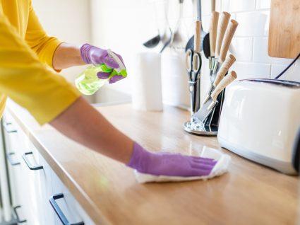 pessoa a limpar o balcão da cozinha e fazer outras tarefas domésticas