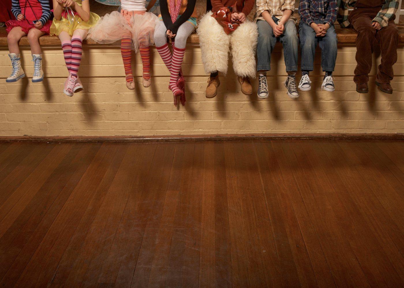 crianças vestidas de personagens sentadas no palco