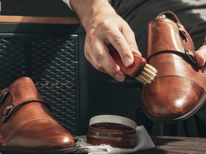 homem a limpar sapatos de pele com escova própria