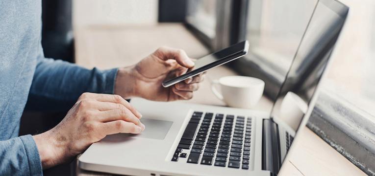 homem usa computador e iphone
