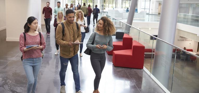 estudantes a conversar no corredar da universidade
