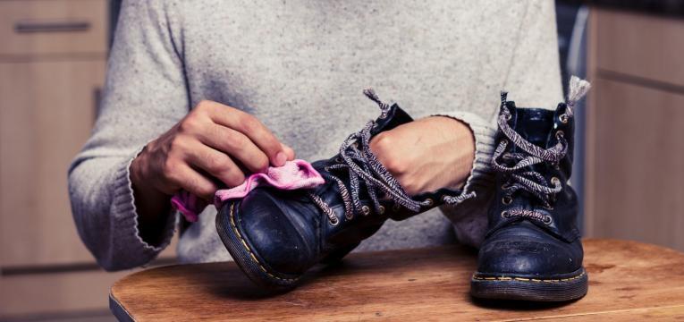 jovem a aprender como limpar sapatos
