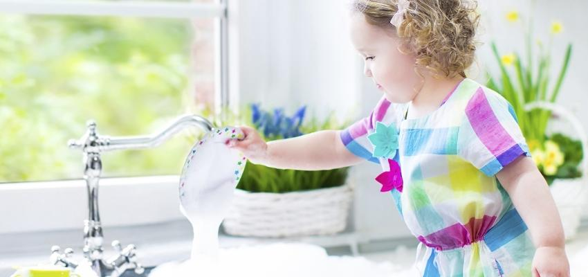 criança a lavar louça na banca