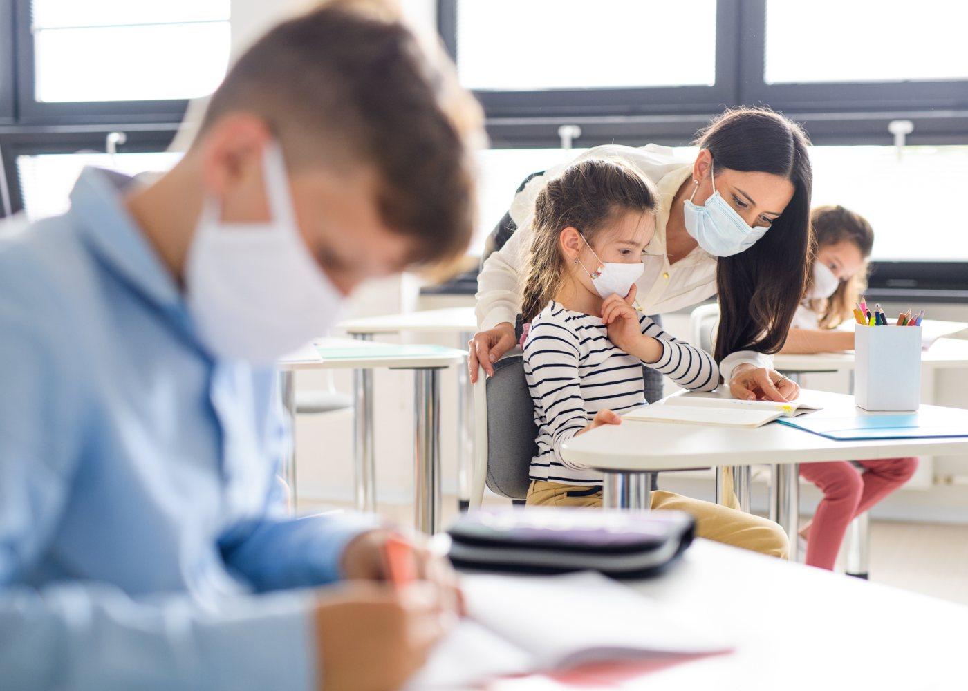 crianças com máscara em segurança no regresso às aulas