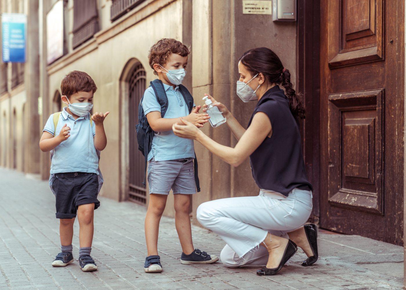 professora a desinfetar mãos a alunos para garantir segurança no regresso às aulas