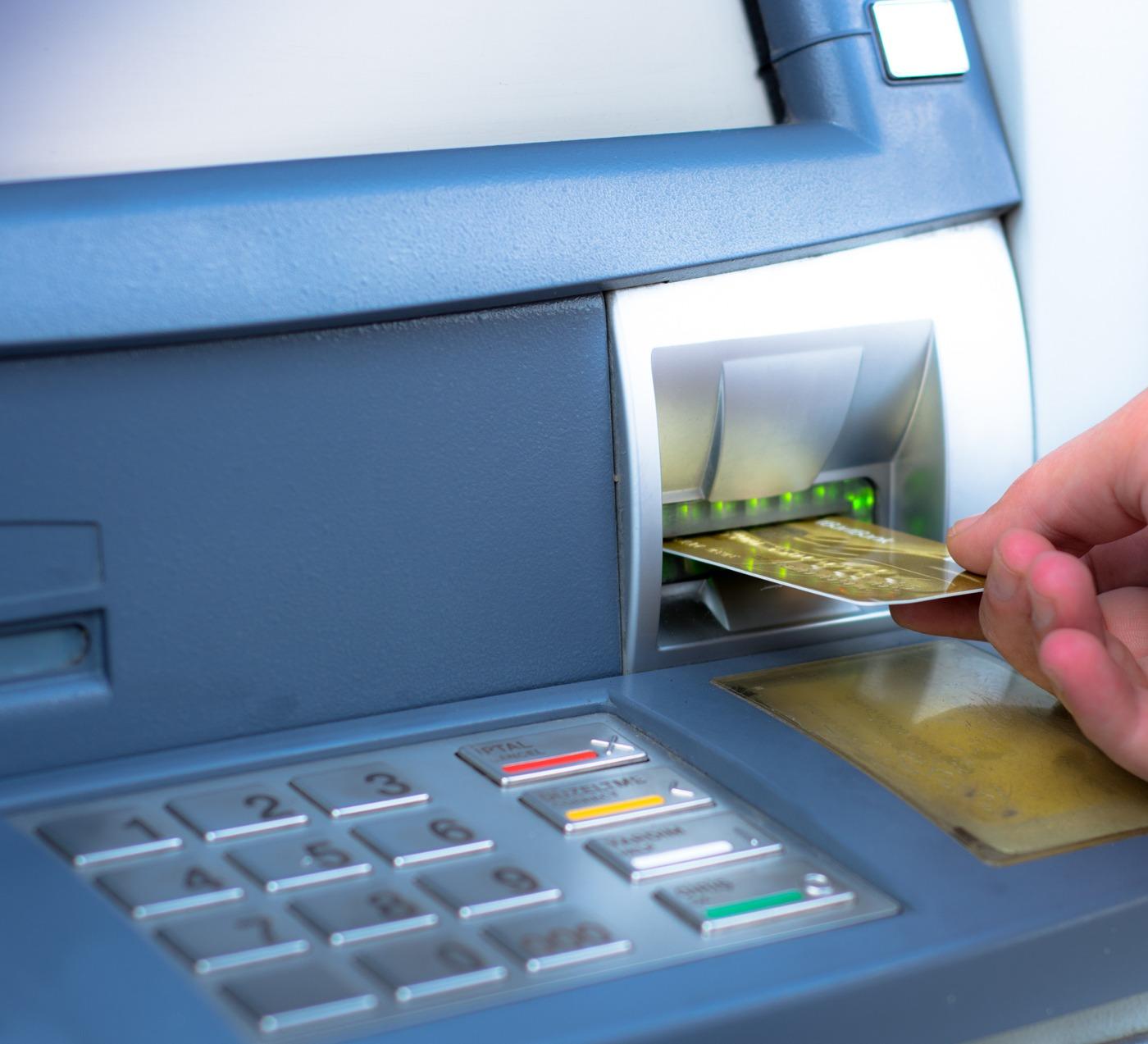 Homem a utilizar cartão de débito numa caixa Multibanco
