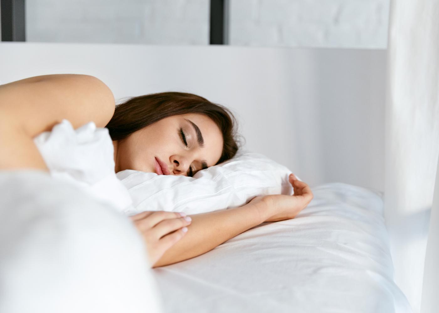 mulher a dormir descansada com a cabeça na almofada