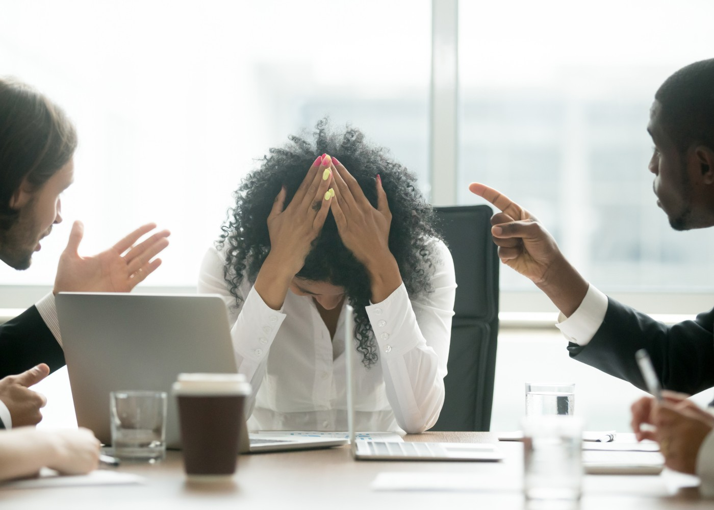 mulher com mãos na cabeça de desepero com dois colegas a falar com ela e apontar dedo