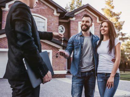 agente a entregar a chave de casa a um casal jovem