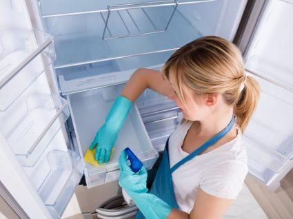 mulher a descongelar o congelador e a limpar