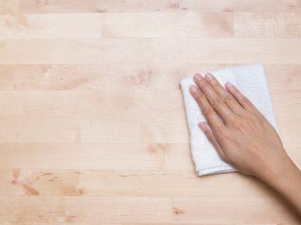pessoa a limpar superfície de madeira com pano