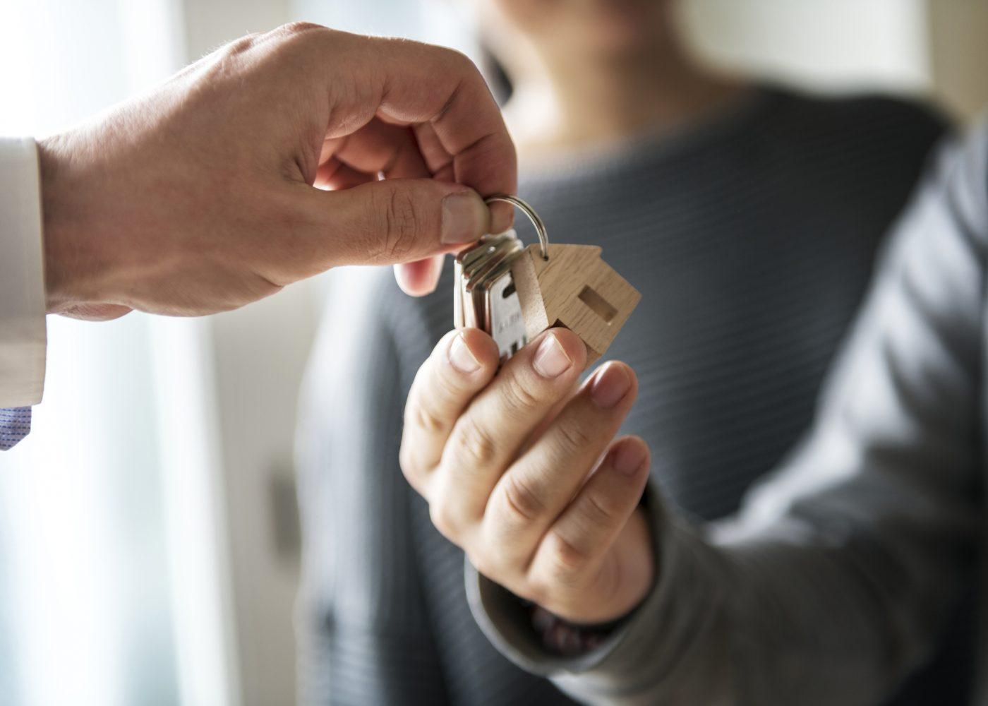 close up nas mãos de uma pessoa a entregar umas chaves de casa a outra