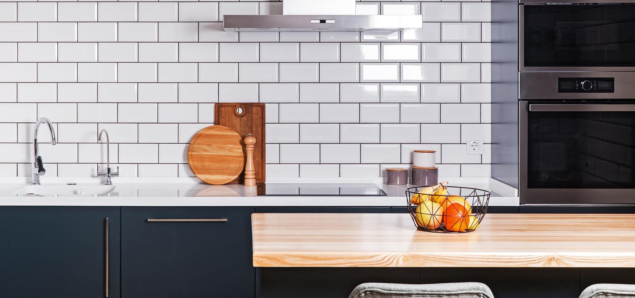 cozinha moderna com parede branca e balcão preto