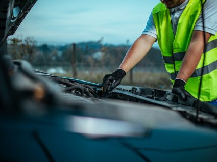 condutor com capot aberto a analisar erros de condução que podem causar avarias no carro