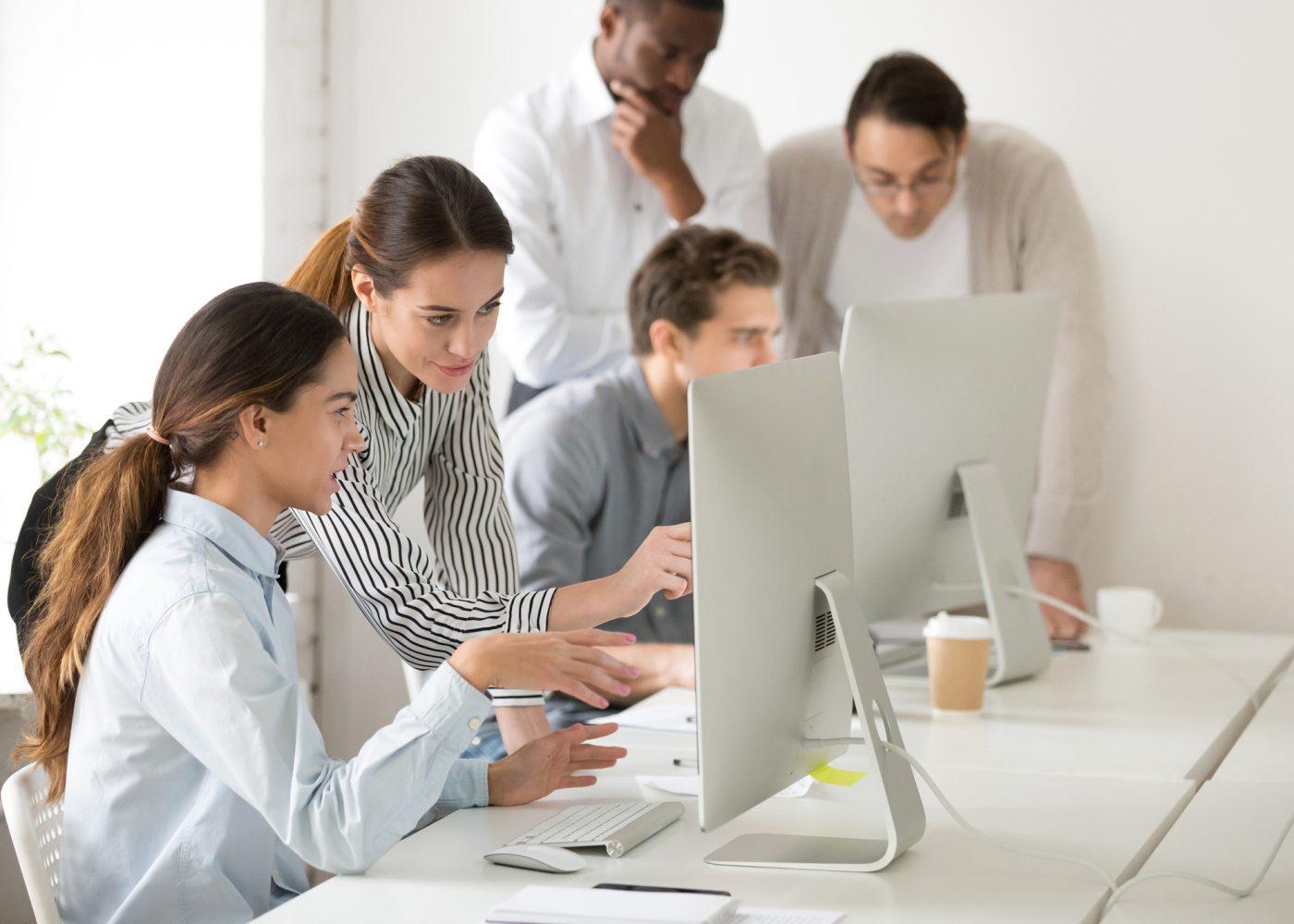 pessoas ao computador a trabalhar em equipa