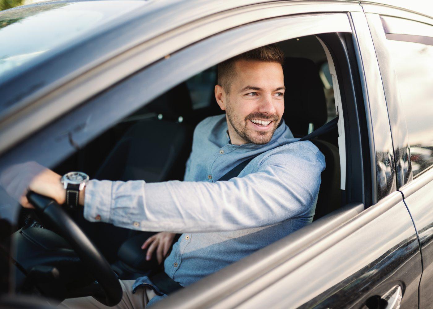 homem a sorrir ao volante de um carro