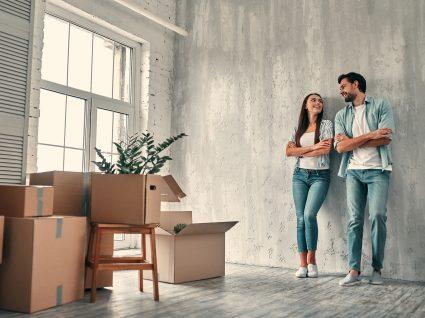casal na casa nova encostado à parede com caixas por arrumar
