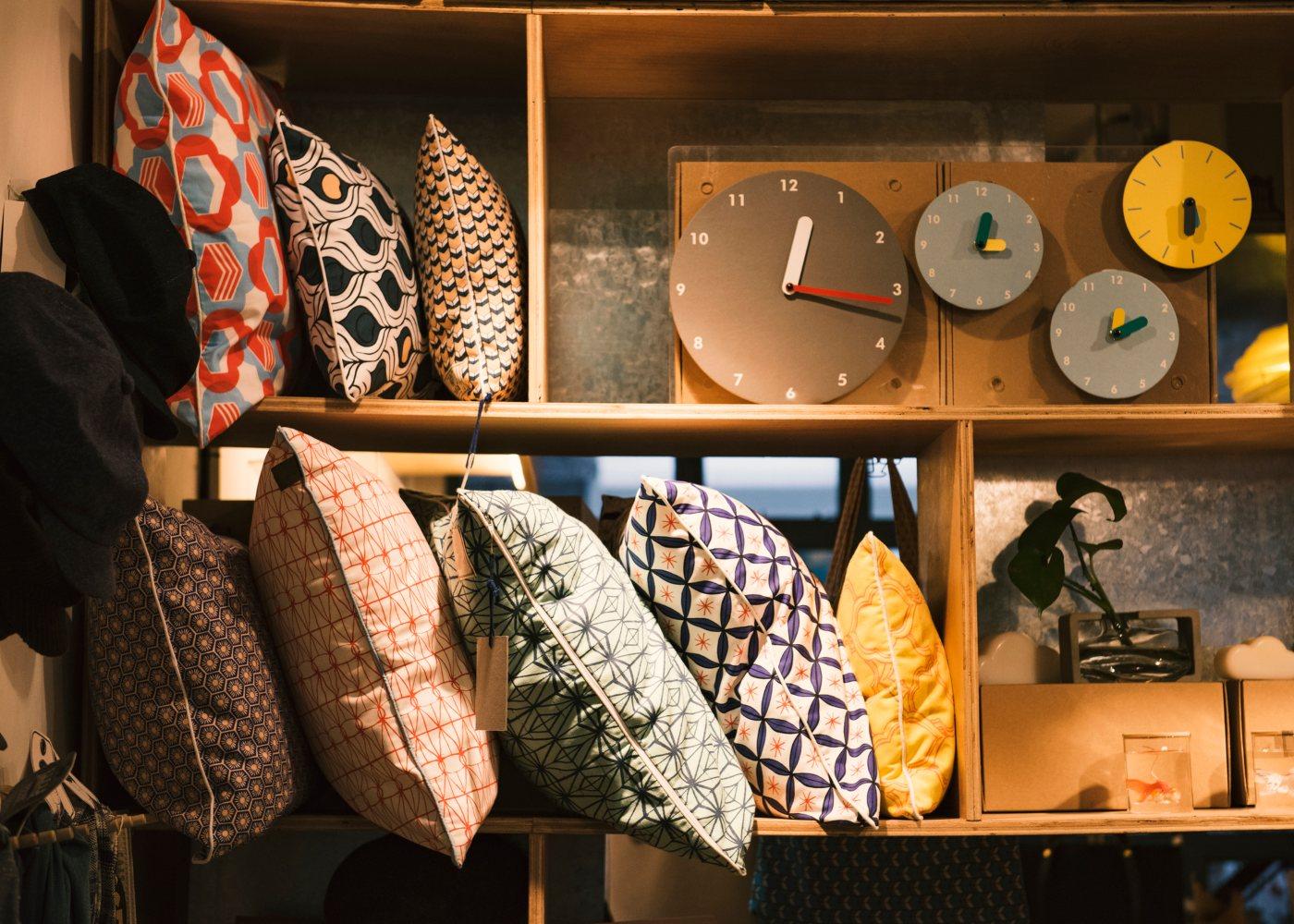 almofadas e outros itens decorativos expostos em prateleiras