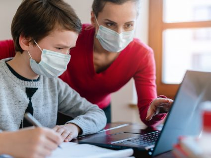 Regresso às aulas: guia para pais - mãe e filho de máscara a fazer trabalhos no computador
