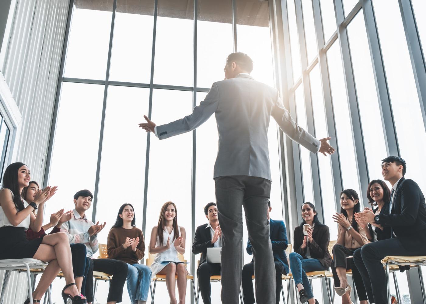 grupo de pessoas a ouvir homem a falar numa reunião