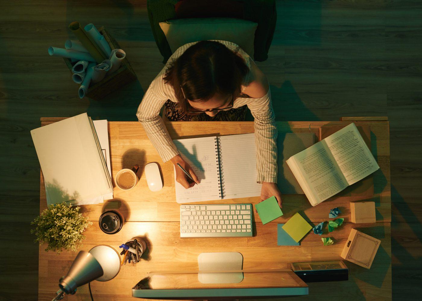 vista de cima de uma jovem a estudar e todo o material