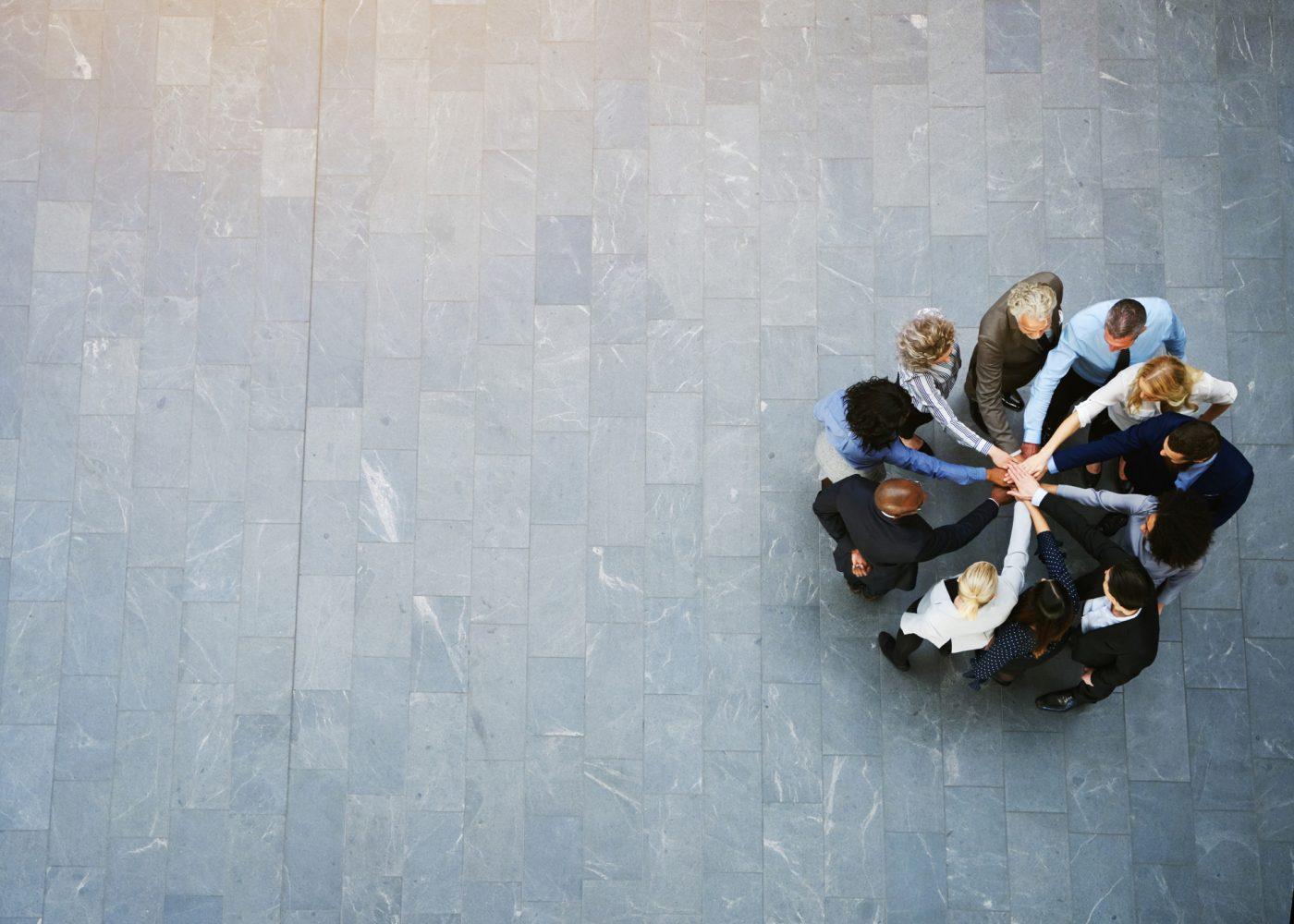vista de cima de trabalhadores unidos com mãos ao centro